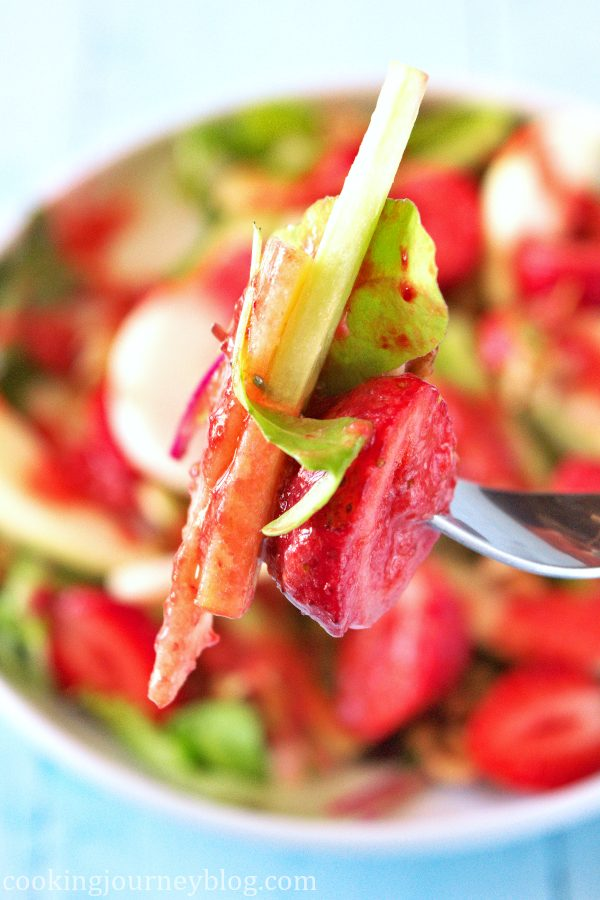 Strawberry summer salad on a fork