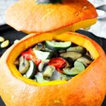 Stuffed pumpkin with baked vegetables is beautiful and healthy meal. Orange pumpkin, stuffed with zucchini, eggplant, mushrooms and red bell pepper.