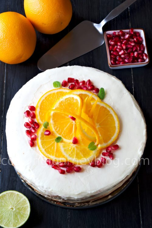 Orange cake is great birthday cake or beautiful and tasty table decoration. Chocolate sponge with crunchy pavlova, the most delicious orange jam you can imagine, and white cream frosting with a hint of rum. Beautiful rustic cake. View from top. White rustic cake with oranges and pomegranate.