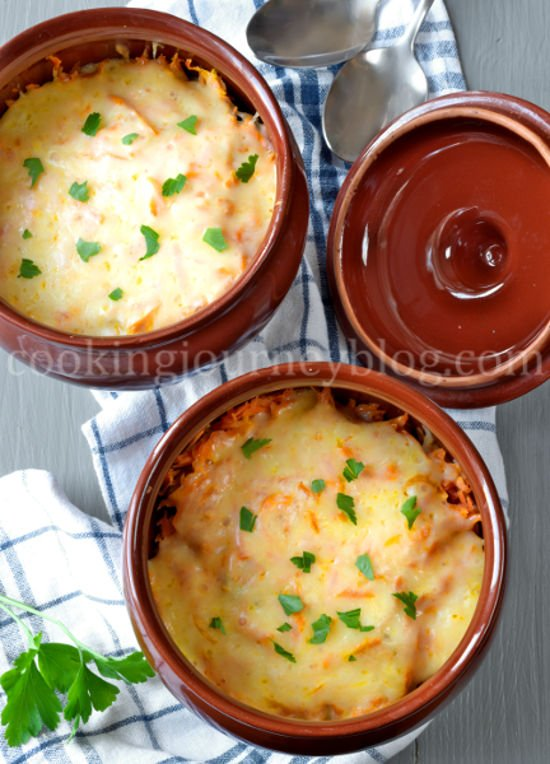Dinner in two clay pots. Beef and potatoes, covered with cheese and parsey.