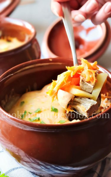 Dinner Ideas . Dinner in a clay pot. Beef and potatoes, covered with cheese and parsey in a spoon.