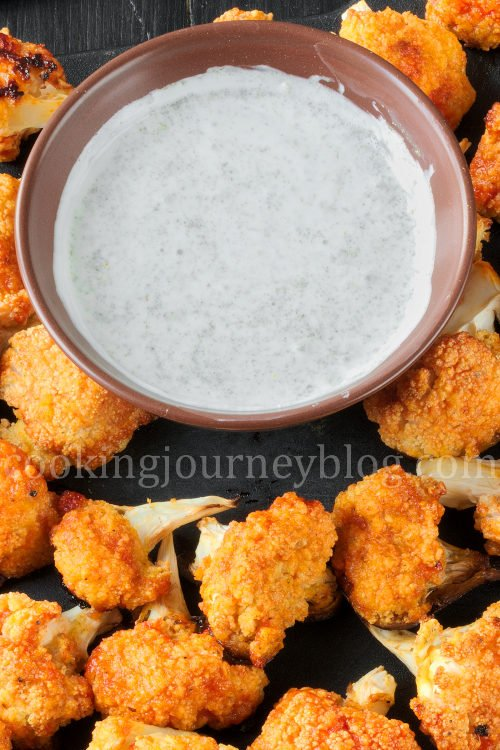 Buffalo cauliflower on a black board, served with white sauce