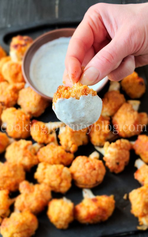 Buffalo cauliflower wings, dipped in white sauce.