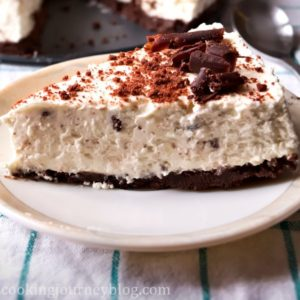 Baileys cheesecake slice on a plate, decorated with chocolate, with a spoon