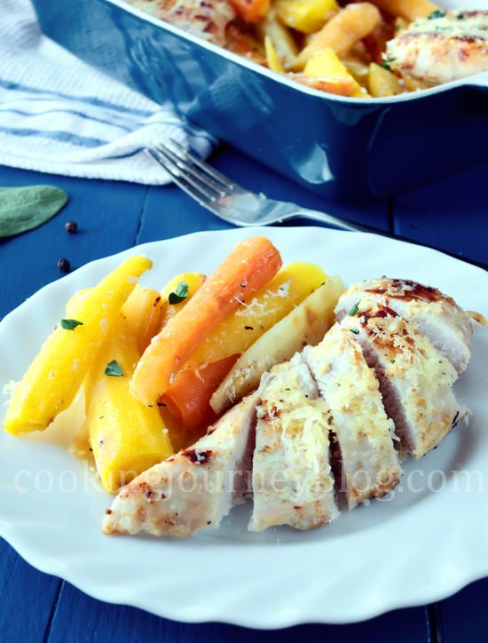 Baked chicken breast, cut and served on a white plate with colorful roasted carrots