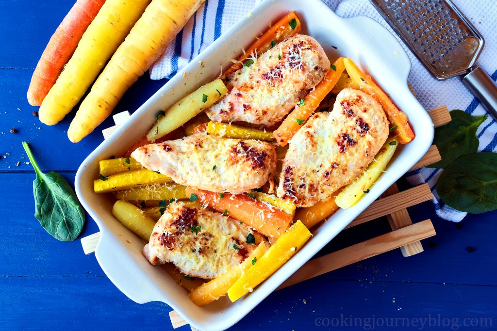 Baked chicken breasts and roasted baby carrots in a baking dish, served on a blue table