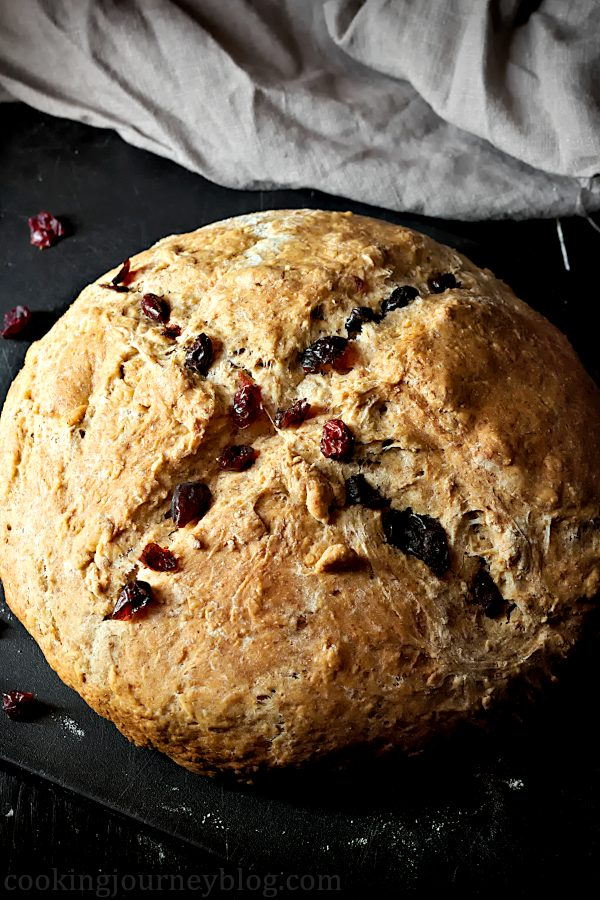 Irish Soda Bread Recipe – How To Make Bread . Irish soda bread with cross and cranberries on a black board.