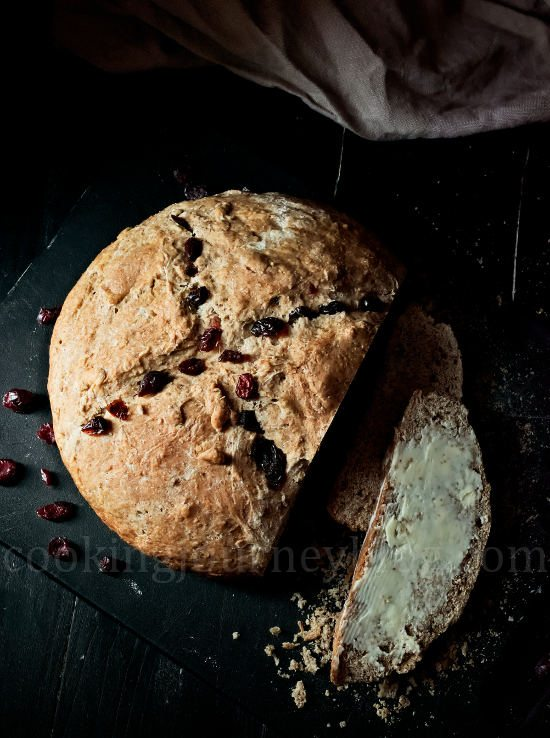 Irish Soda Bread Recipe – How To Make Bread. Irish soda bread with buttter and cranberries on a black board. View from top. Light from the window.