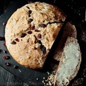 Irish soda bread with buttter and cranberries on a black board. View from top.