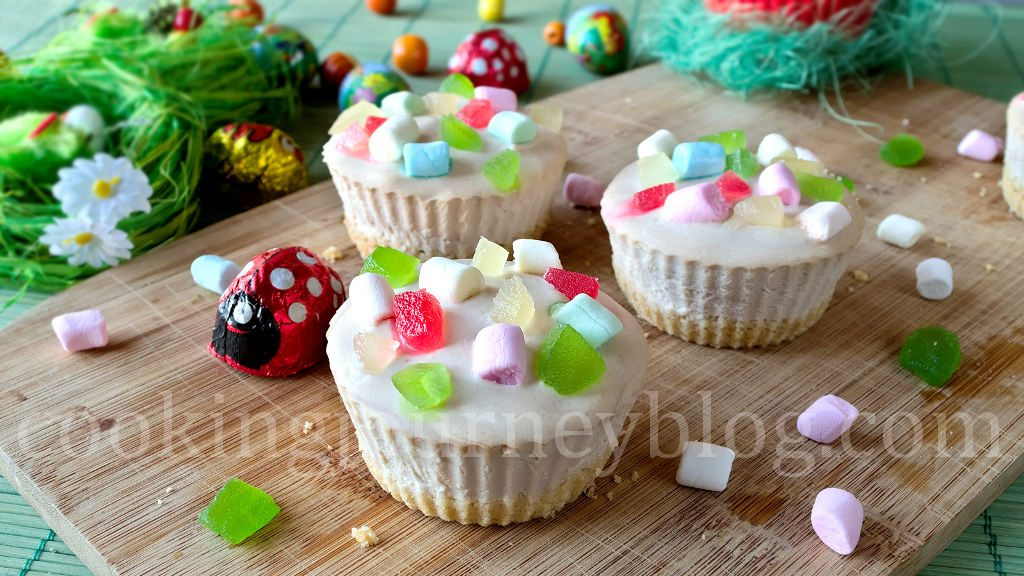 Mini cheesecake with colorful marshmallows served on a wooden board