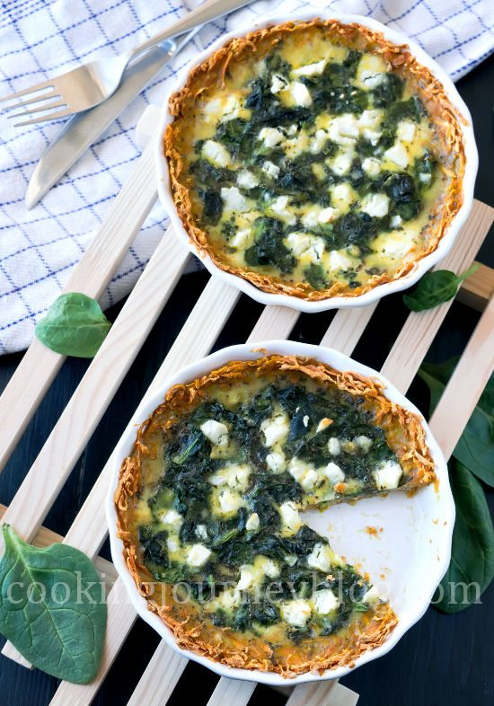Spinach quiche, served on wooden board on the black table. One slice is missing.