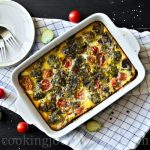 Breakfast frittata with mushrooms, Brussels sprouts and tomatoes, served on a black table right from the oven