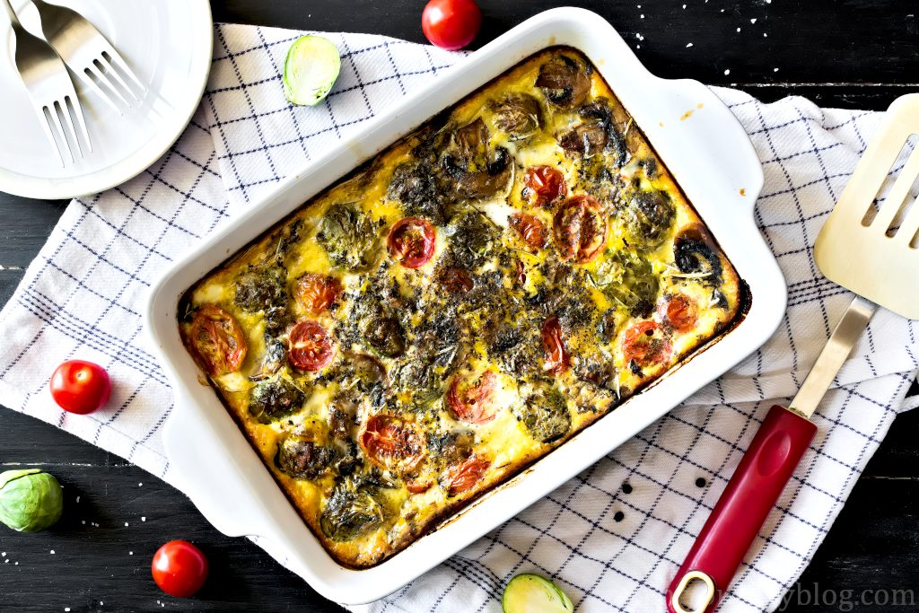 Breakfast frittata with mushrooms, Brussels sprouts and tomatoes, served on a black table in baking dish