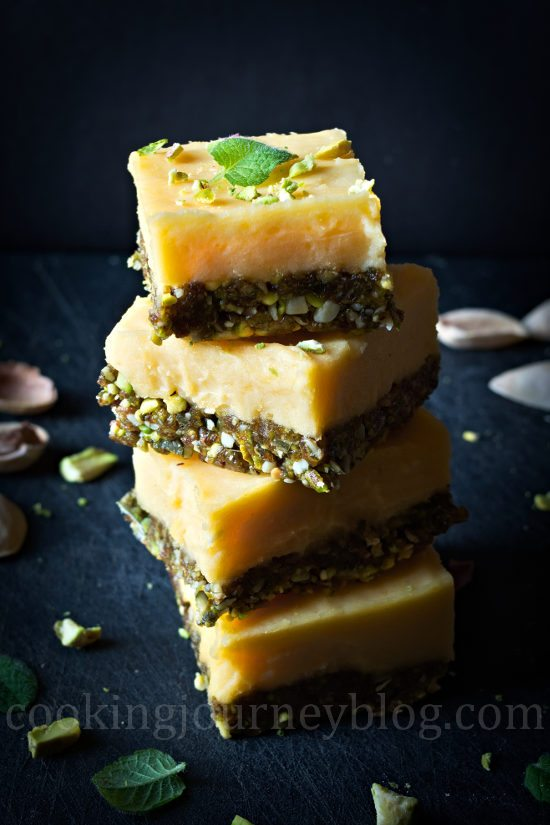 Lemon squares, stack on the black board with pistachios and mint