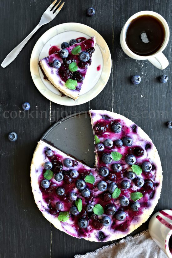 Blueberry cheesecake with fresh berries on top, one slice on a plate, served with cofee. View from top