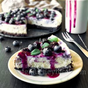 Fresh Blueberry Cheesecake slice on the plate, served with blueberry sauce