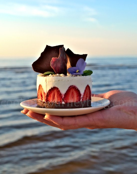 Holding No Bake Greek Yogurt Dessert in one hand on the seaside
