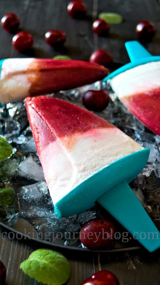 Homemade sugar free popsicles, served with ice, mint and cherries on the black table