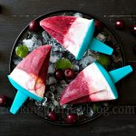 Homemade sugar free popsicles, served with ice, mint and cherries for three persons, view from top