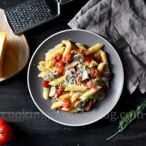 Creamy Mushroom Pasta with Tomatoes, cheese and dill, served on gray plate on black table