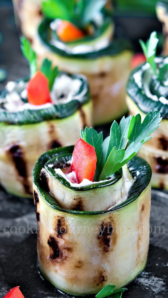 Grilled Zucchini Roll Ups with rerd bell pepper and parsley on black table
