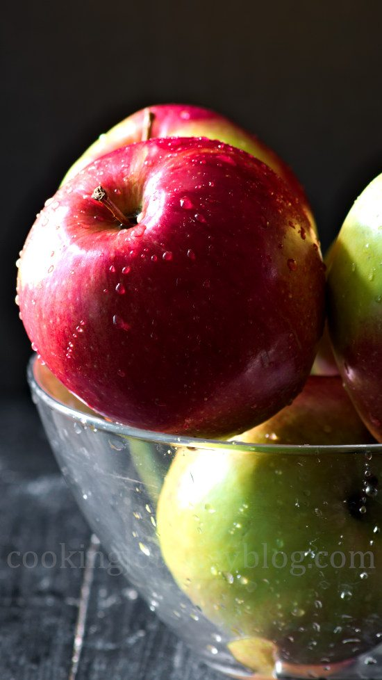 Fresh green and red apples with water drops in a glass bowl