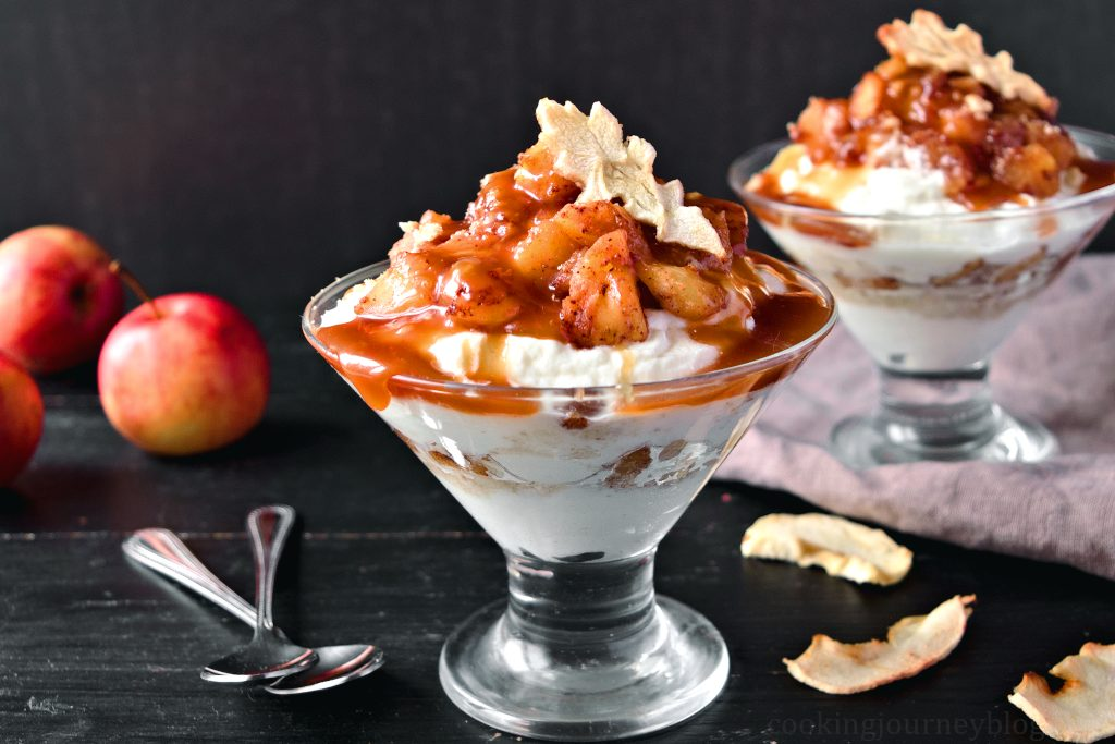 Caramel Apple Trifle with cinnamon apples, whipped cream and dried apples, placed on the black table with spoons