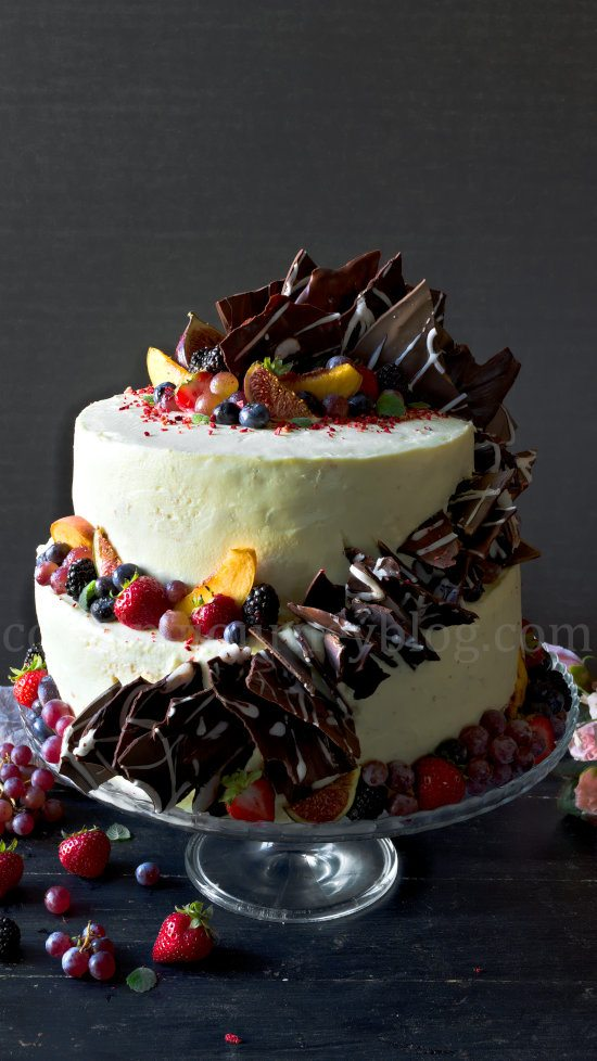 Peach cake with cream cheese frosting, decorated with chocolate and fruits.