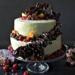 Peach Cake with Cream Cheese Frosting – 2 Tier Cake on a black table, with fruits on a cake stand
