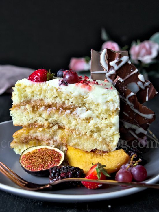 Peace of peach cake with Cream Cheese Frosting, chocolate and fruits. Placed on grey plate.