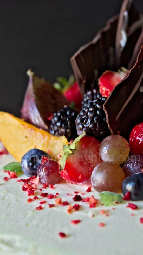 2 tier cake decorated with chocolate and fruits - peaches, grapes, blueberries, strawberries and dried strawberries
