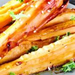 Honey Roasted Parsnips with sesame and kale on a grey plate