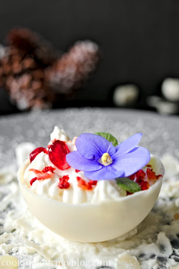Chocolate Ball, decorated with pomegranate, mint and violet flower. Winter dessert, view from the side. Christmas tree cons on the background.