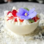 Chocolate Ball, decorated with pomegranate, mint and violet flower. Winter dessert, view from the side.