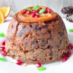 Christmas Pudding, served on a plate with pomegranate seeds and orange, served on the plate.
