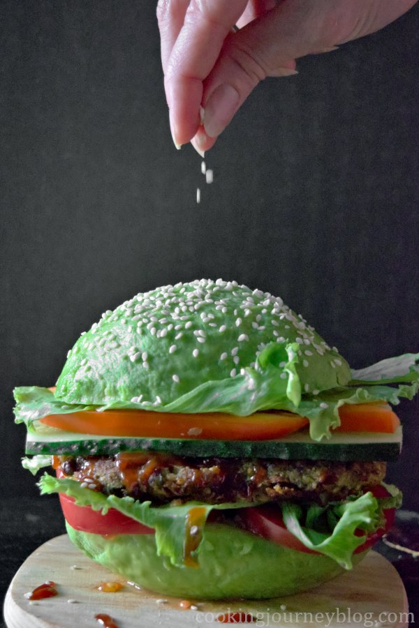 Sprinkling sesame seeds on vegan avocado burger