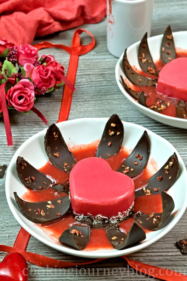 Mirror glaze cake, blooming with chocolate leaves and strawberry sauce on a plate for Valentine's day.