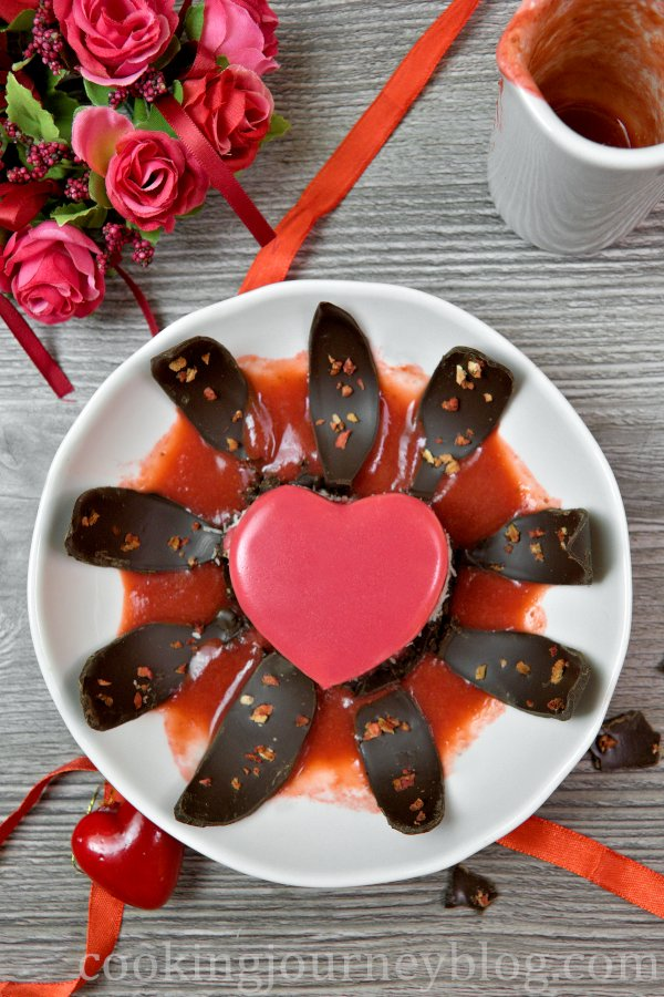 Plated Valentine's desserts, red mirror glaze cake on a plate with opwnwd chocolate leaves and strawberry desserts.