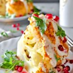 Whole roasted cauliflower with tahini sauce, pomegranate seeds and parsley.