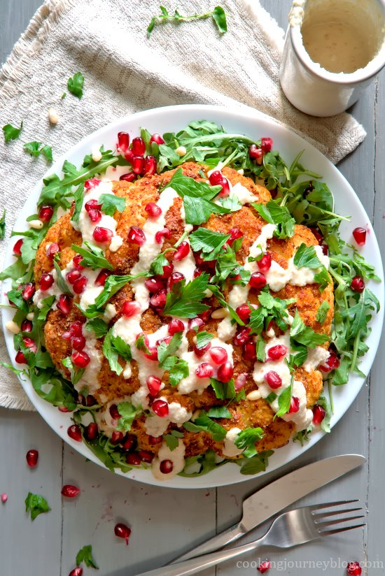 Whole roasted cauliflower with tahini sauce, pomegranate seeds and parsley. View from top.