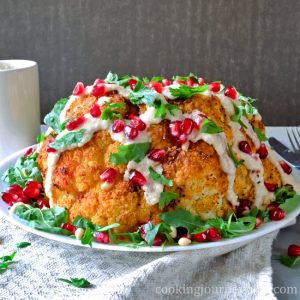 Whole roasted cauliflower with tahini sauce, pomegranate seeds and parsley. Served with some extra tahini sauce.