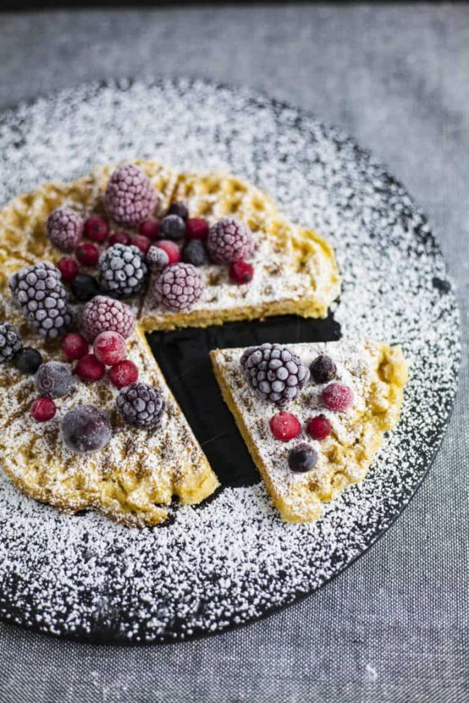 crispy vegan waffle served on a dark plate with berries on top, dusted with icing sugar