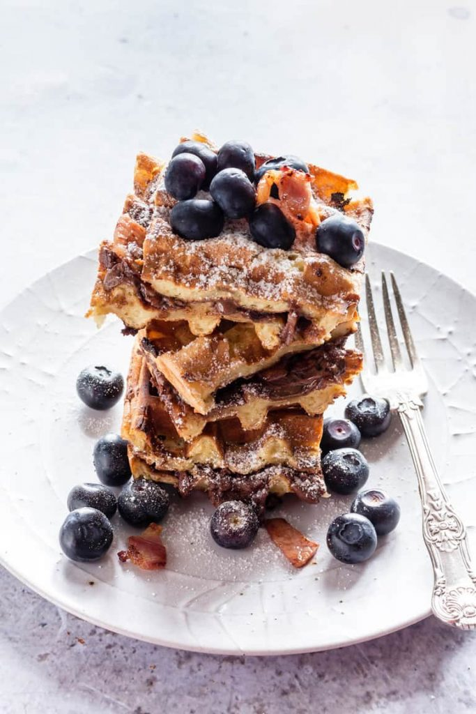 Waffle stack with nutella and blueberries, served on a white plate with a fork