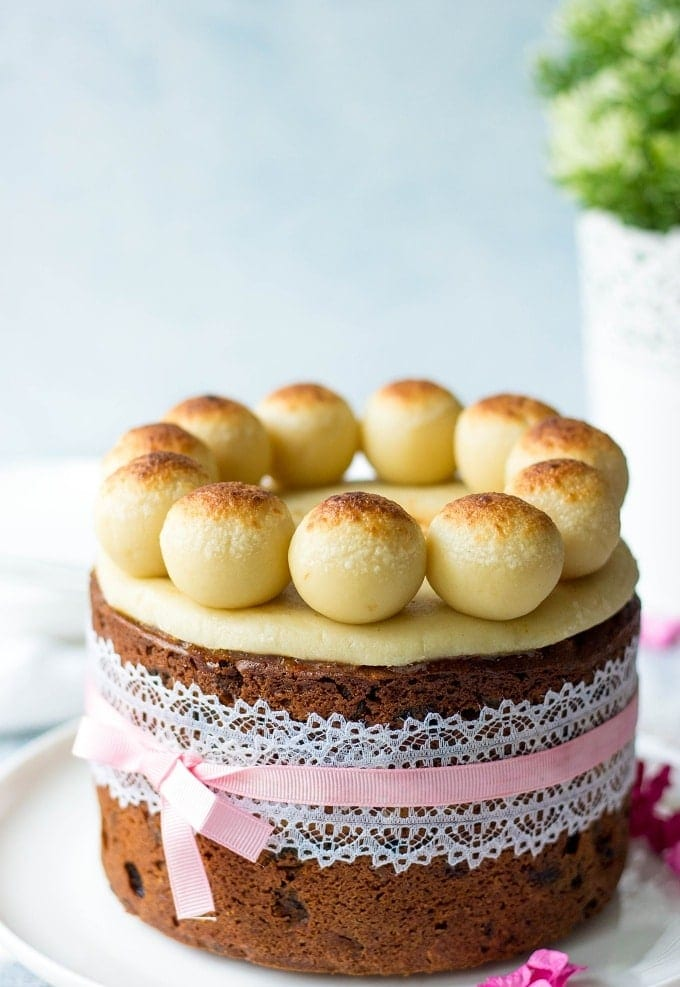 Simnel Cake, decorated with white lace and pink ribbon
