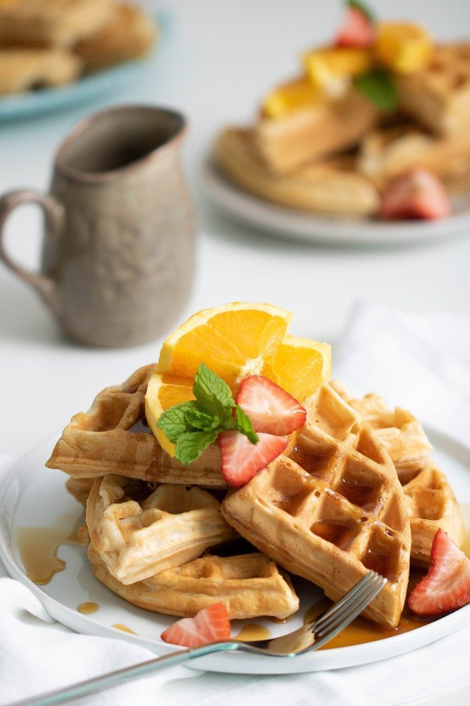 Vegan Orange Belgian Waffles on a white plate, served with orange and strawberry slices