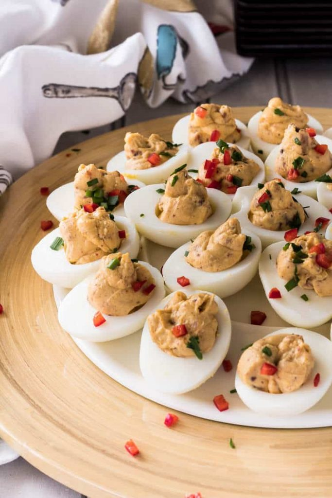 Maple Bacon Deviled Eggs served on a wooden plate