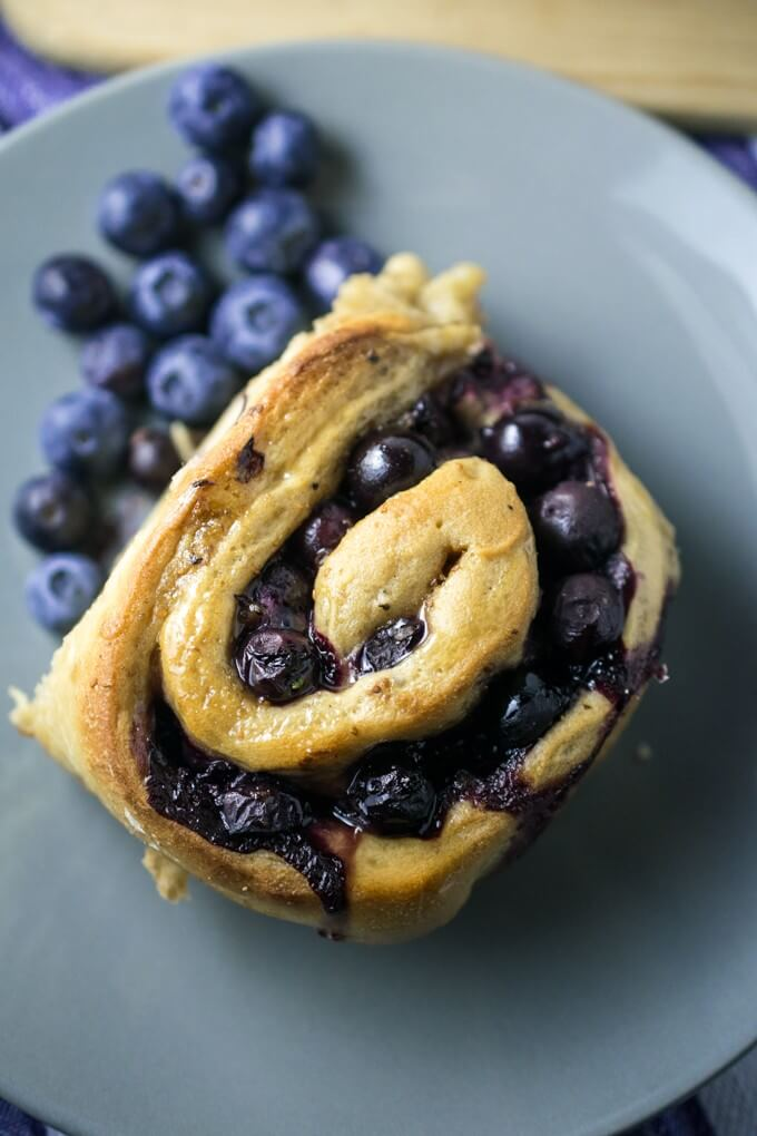Blueberry roll on a plate served with fresh berries