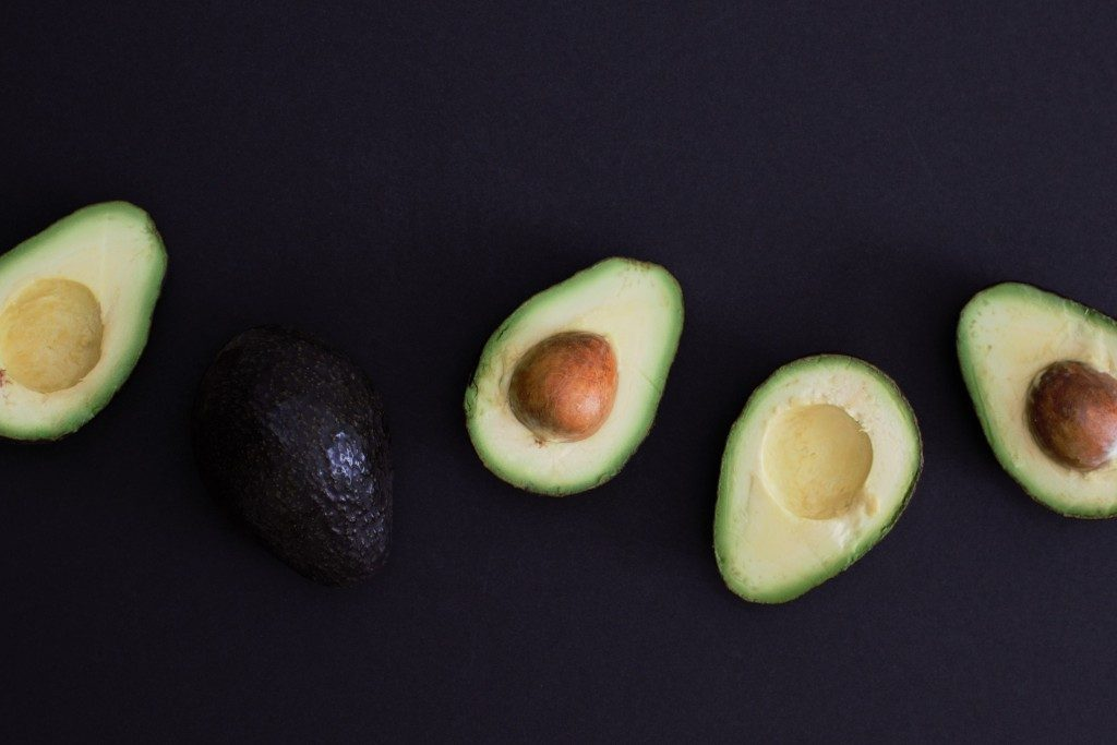 5 Health Benefits of Avocado. Avocado, cut in half on a black table