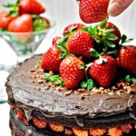 Vegan Chocolate Cake, decorated with strawberries. Served on a white table with red ribbon on the table.