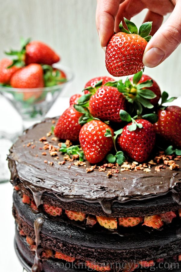 Decorating vegan chocolate cake with strawberries